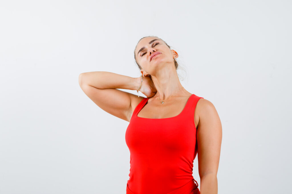 young female holding hand on neck in red tank top, pants and looking exhausted. front view.